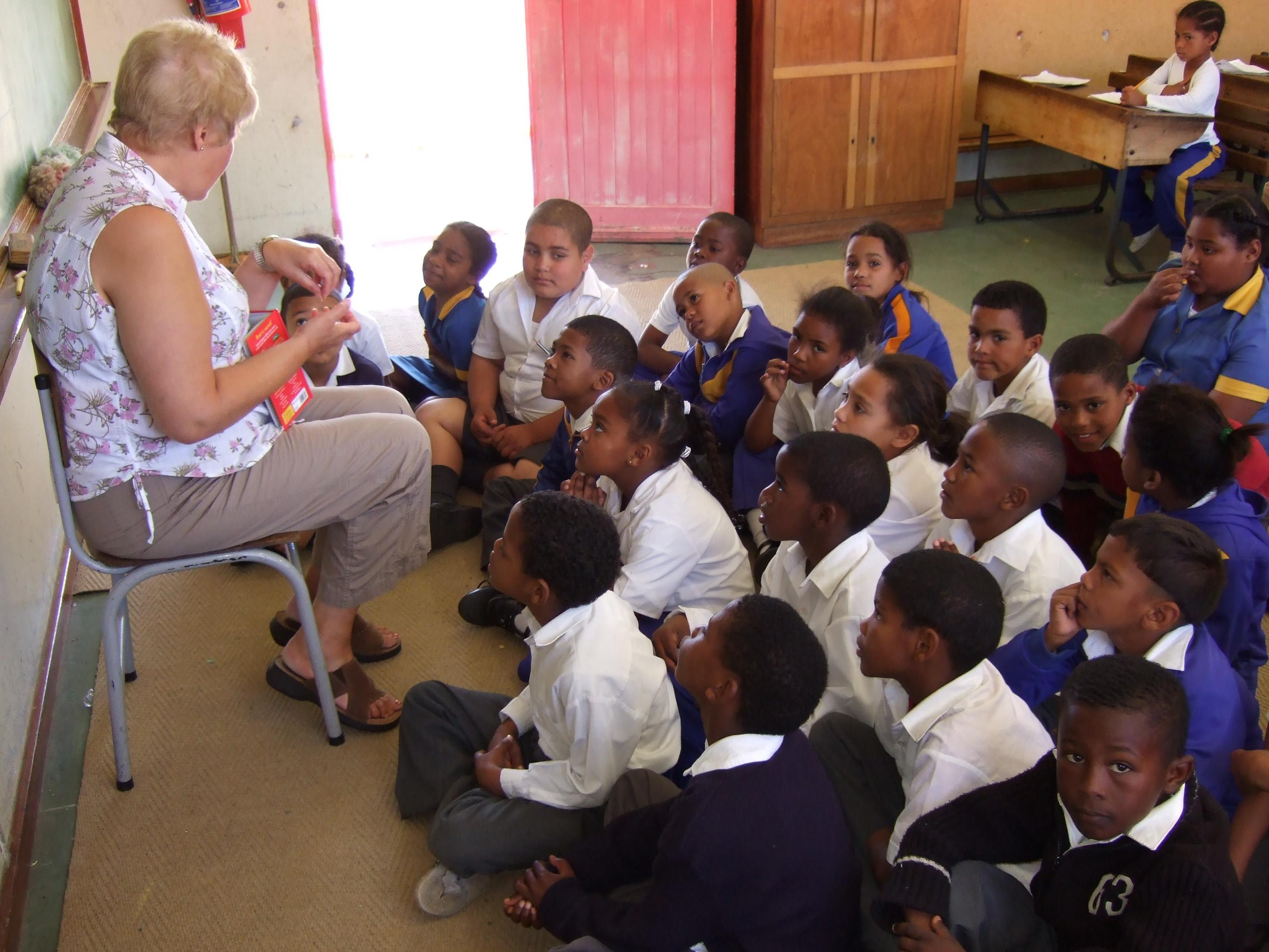 Young students listen to a Projects Abroad volunteer as a teacher in South Africa